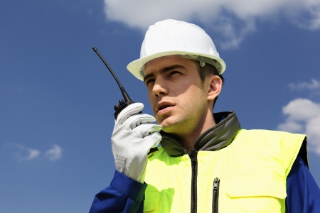 portrait of builder with transmitter in blue sky Stock Photo