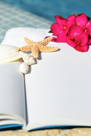 book, starfish, shellfish and white towel beside a pool  photo