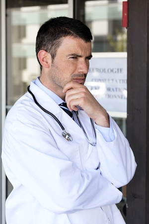 pensive doctor with stethoscope in front of hospital photo