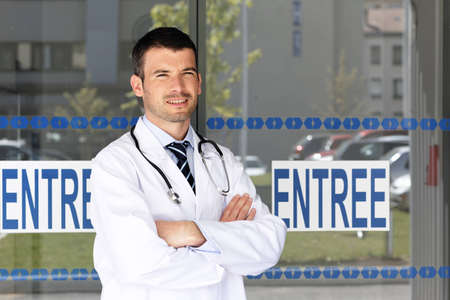 handsome doctor in front of hospital entry photo