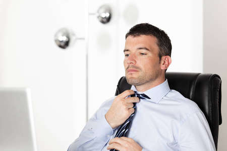 handsome businessman readjusting his tie in office photo