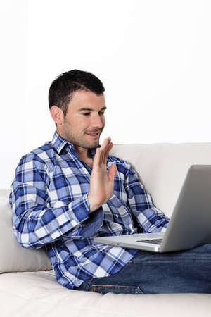 Portrait of a man waving at a laptop photo