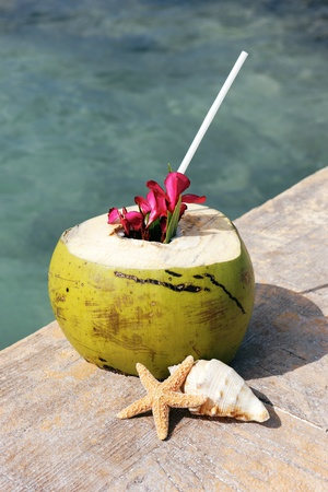 Coconut with drinking straw on a beach in summer  photo
