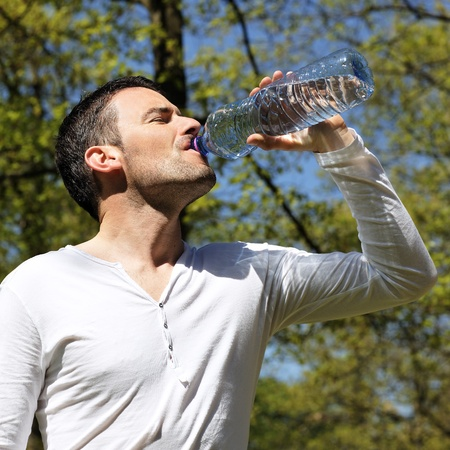 zomers drankje: knappe man drinkwater in een park Stockfoto
