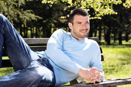 thirties portrait: relaxed man on  a bench in spring Stock Photo