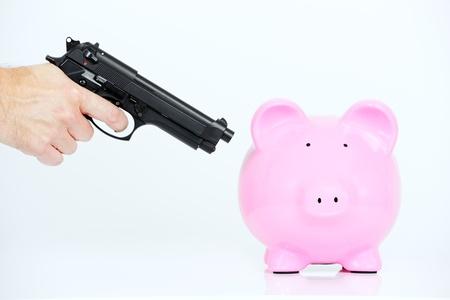 hand gun: pink piggy bank and hand with gun Stock Photo