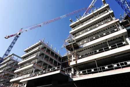 building structures: construction site with cranes and blue sky