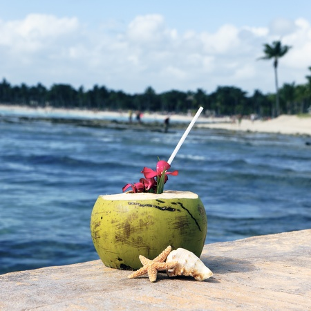 Coconut cocktail with drinking straw on a beach in Mexico photo