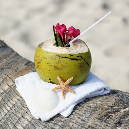 Coconut cocktail with drinking straw on a palm tree on a beach photo
