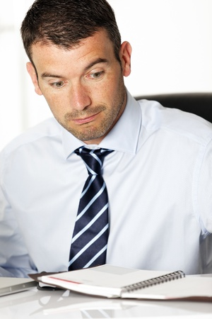 surprised man in office loking at his diary Stock Photo - 13568803