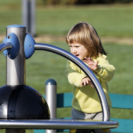 child playing on playground in a park in autumn photo