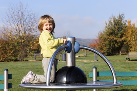 child playing on playground in a park Imagens