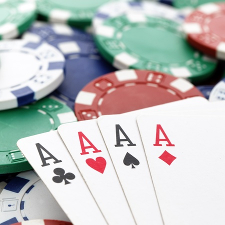 hold em: four aces of a kind with chips background