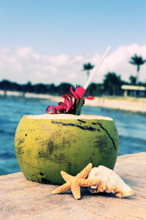 Coconut with drinking straw at the sea  photo