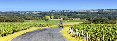tractor with trailer on the road in autumn, panoramic view photo