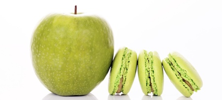 green apple with macaroons on white background, panoramic photo