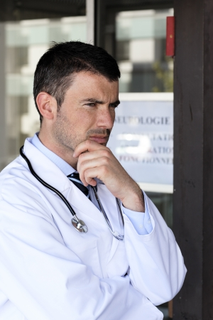 pensive doctor with stethoscope at hospital photo