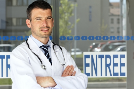 young handsome doctor in front of hospital entry photo