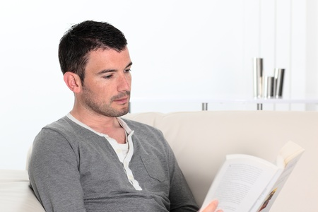 man reading a novel book while relaxing on sofa  photo