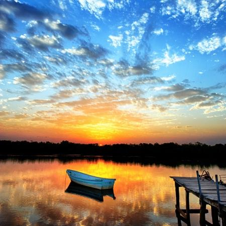 turismo ecologico: peque�o bote en el lago en la puesta del sol