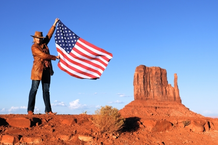 young beautiful woman holding USA flag at Monument Valley photo