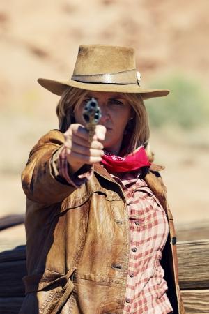 mujer con pistola: Cowgirl con un arma en la mano