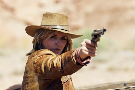 brown leather hat: bad girl with a gun in the hand Stock Photo