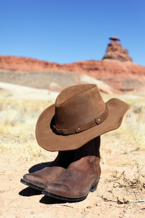 boots and hat in front of mexican hat rock photo