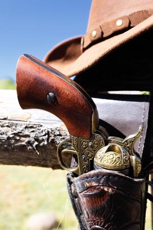 old west: gun and hat outdoor under sunlight in autumn