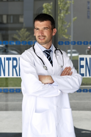 young doctor in front of hospital entry photo