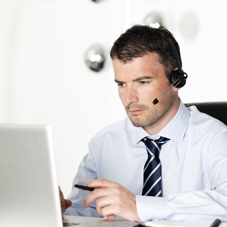 telephone headsets: man in office with laptop and headset on his head