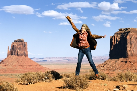 western wear: happy cowgirl jumping at Monument Valley, Utah, USA Stock Photo