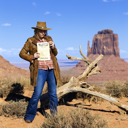 jane: bad cowgirl holding wanted paper at Monument Valley