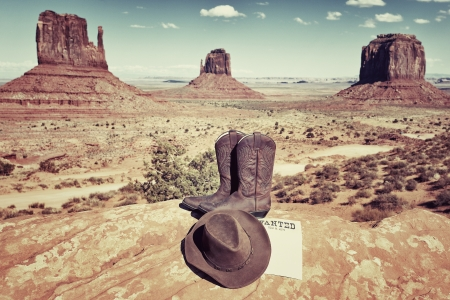boots and hat in front of famous Monument Valley, USA photo