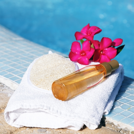 massage oil: massage oil on white towel beside a pool