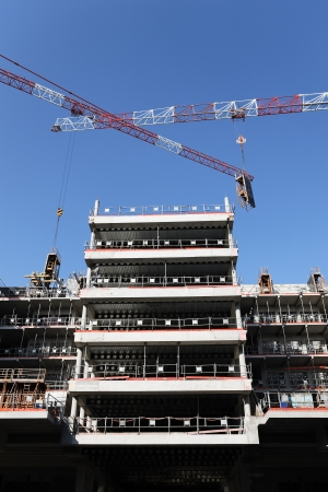 vertical view of building site with crane in blue sky