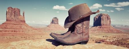 boots and hat in front of Monument Valley, USA, panoramic view photo