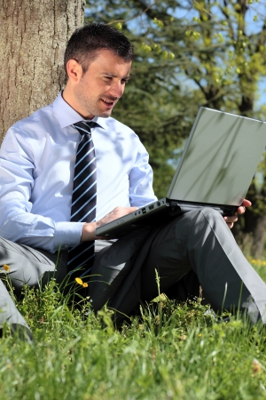 young businessman working with laptop in a park photo
