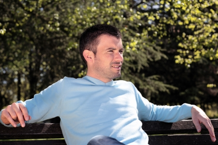 early 30s: handsome man resting on a bench in a park