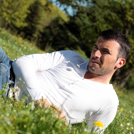 early 30s: handsome man with daisy in a park