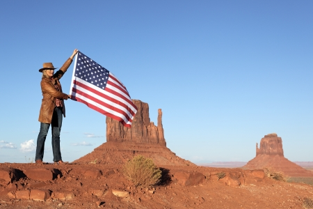 beautiful blond woman holding USA flag at Monument Valley photo
