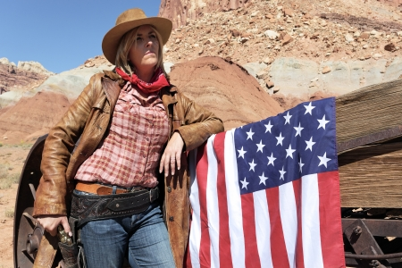 portrait of a young blond cowgirl with american flag photo