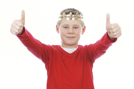 Young boy with crown giving you thumbs up isolated on white background  photo