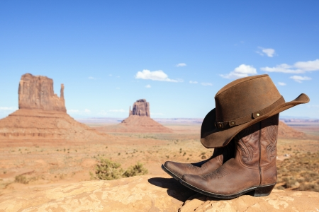 cowboy boots and hat in front of Monument Valley, USA, panoramic view