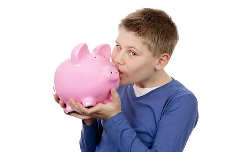 boy kissing pink piggybank on white background photo
