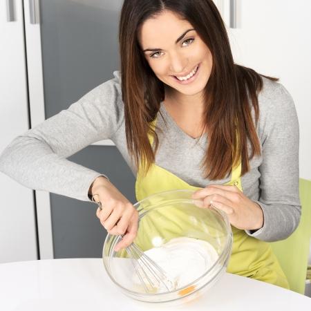 crepas: Hermosa mujer batiendo la masa en la cocina