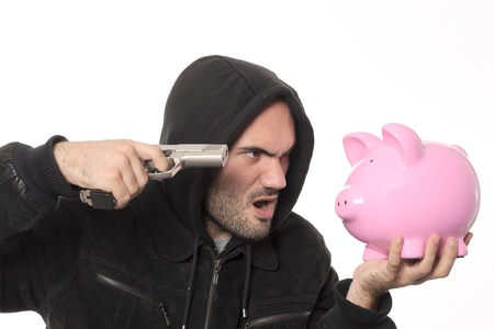 man with gun and pink piggy bank in studio photo