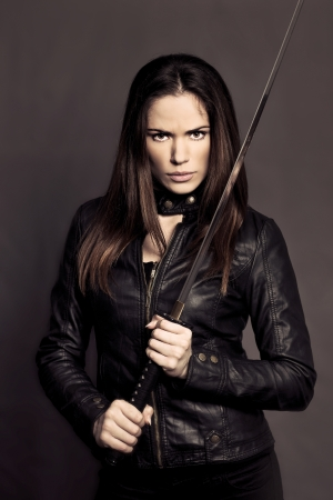 Beautiful girl with Katana in studio photo