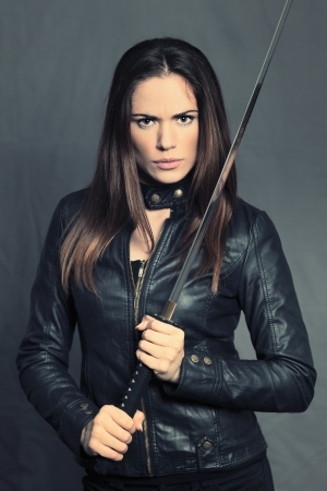 Dangerous girl with Katana in studio photo