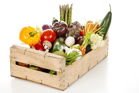 Assortment of fresh vegetables in a crate on white background photo